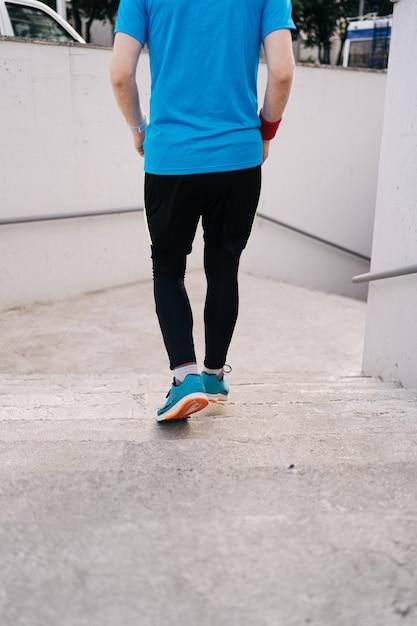 Jonge mensenbenen die intervaltraining op treden uitoefenen Gratis Foto