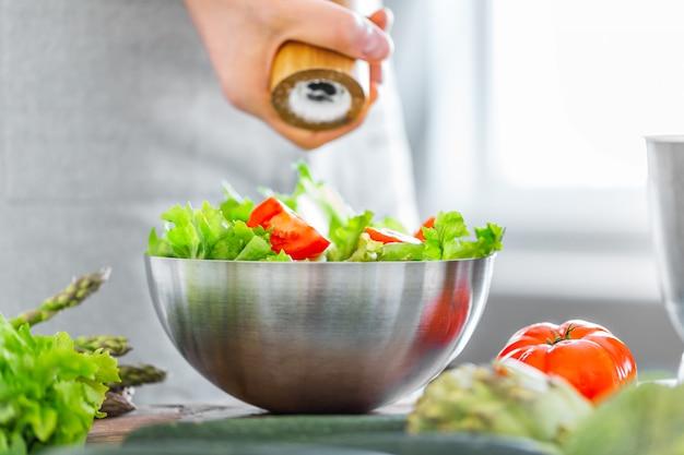 Jonge mensenchef-kok die gezonde salade koken Gratis Foto
