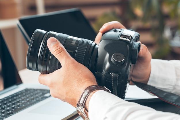 Jonge mensenfotograaf die aan een computer werkt. bureau met toetsenbord, camera, laptop en lenzen. Premium Foto
