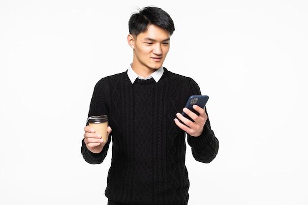 Jonge mensengebruik op mobiele telefoon met koffie op witte muur Gratis Foto