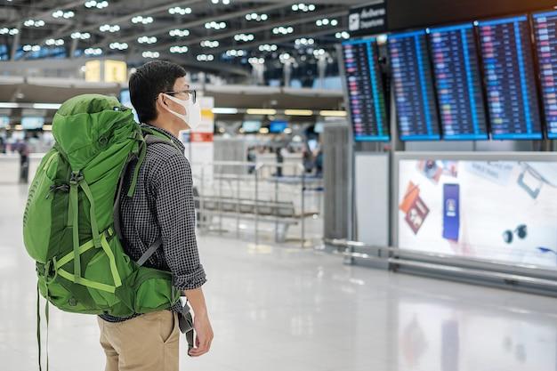 Jonge mensenreiziger die medisch gezichtsmasker draagt en vliegtijd in luchthaventerminal controleert Premium Foto