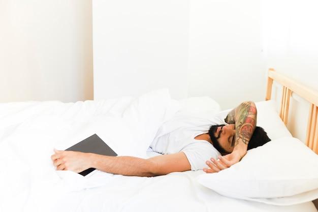 Jonge mensenslaap op bed met digitale tablet Gratis Foto