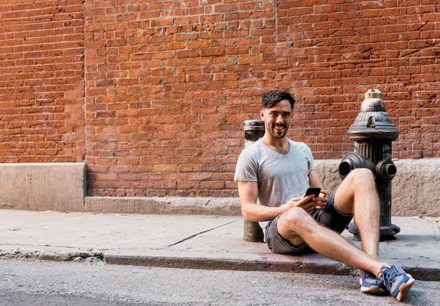 Jonge mensenzitting op stoep mobiel gebruiken Gratis Foto