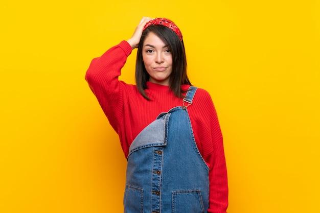 Jonge mexicaanse vrouw met overall over gele muur met een uitdrukking van frustratie Premium Foto