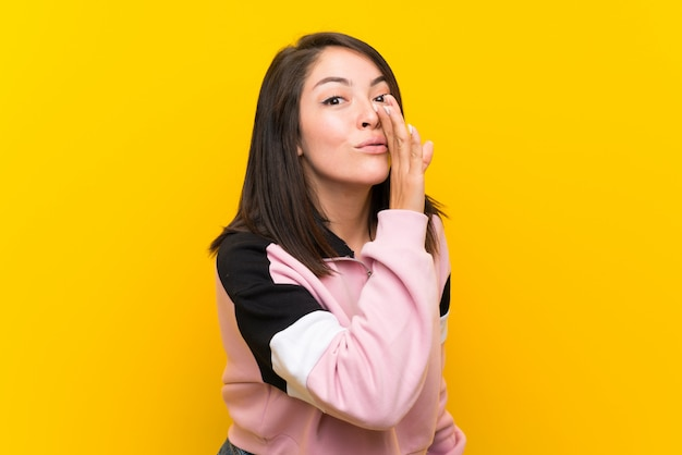 Jonge mexicaanse vrouw over geïsoleerde gele achtergrond die iets fluistert Premium Foto