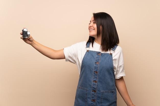 Jonge mexicaanse vrouw over geïsoleerde het maken van een selfie Premium Foto