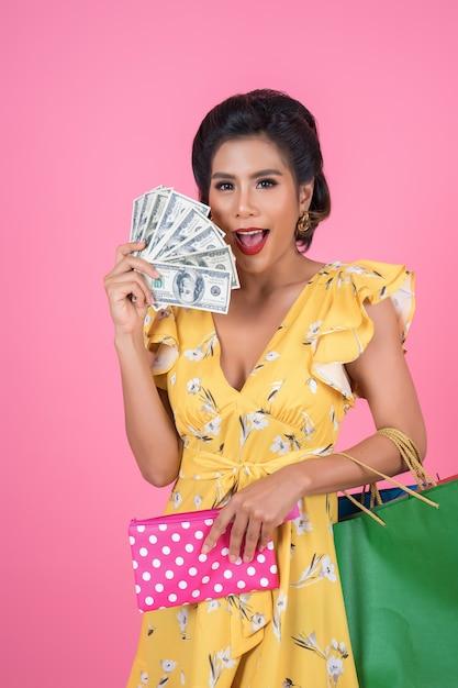 Jonge mode vrouw hand houden portemonnee en boodschappentassen Gratis Foto