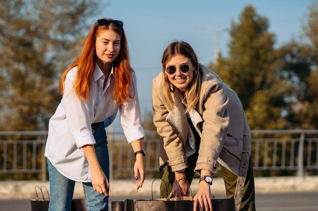 Jonge mode vrouwen met boodschappentassen op parking Gratis Foto