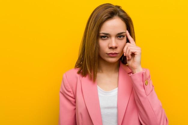 Jonge mode zakelijke vrouw haar tempel met de vinger, denken, gericht op een taak. Premium Foto