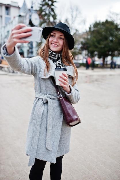 Jonge model meisje in een grijze jas en zwarte hoed met lederen handtas op schouders blijven met plastic kopje koffie Premium Foto