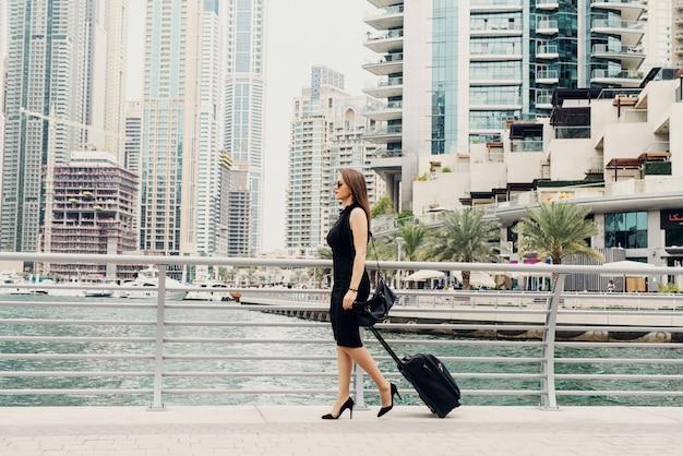 Jonge moderne vertrouwen zakenvrouw trekken een koffer in een dubai marine. een nieuwe baan beginnen in een grote stad. Premium Foto