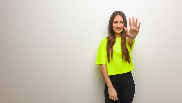 Jonge moderne vrouw die nummer vijf toont Premium Foto