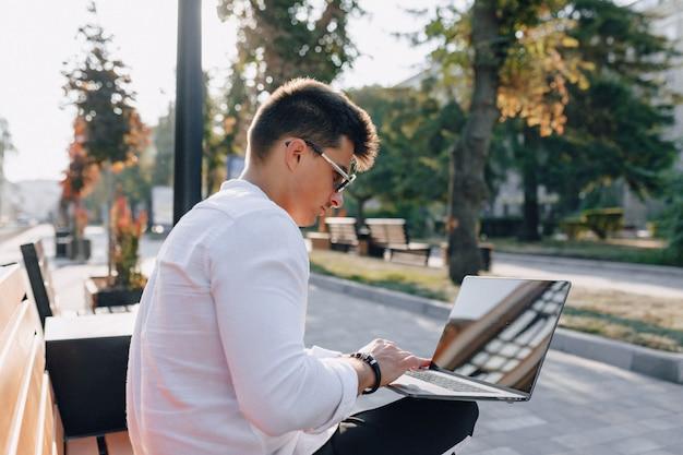 Jonge modieuze kerel in overhemd met telefoon en notitieboekje op bank op zonnige warme freelance dag in openlucht Gratis Foto
