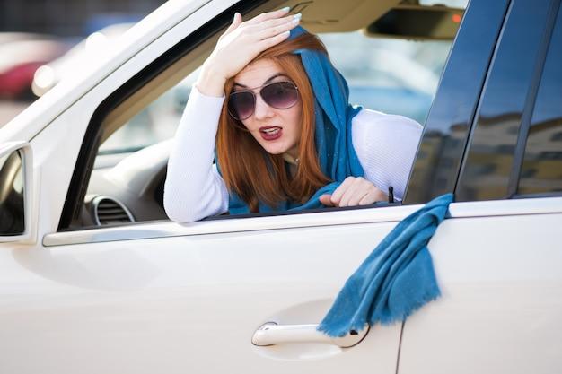 Jonge modieuze vrouw bestuurder heeft haar sjaal vast in voertuig deuren en trekt het uit. Premium Foto