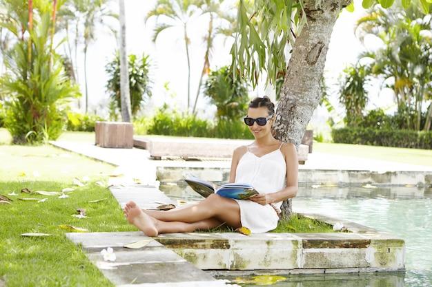 Jonge moeder aanstaande dragen van tinten rust onder boom met tijdschrift in haar handen tijdens vakanties in tropisch land. Gratis Foto