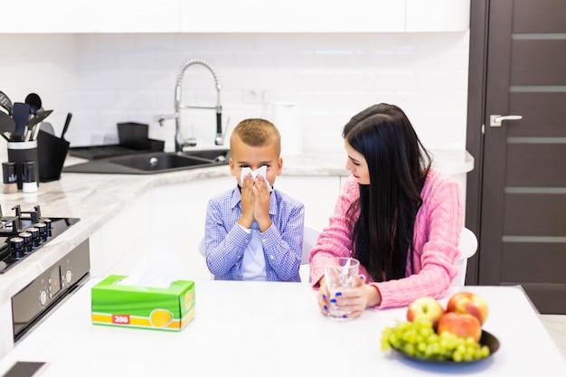 Jonge moeder blijft bij haar zieke zoon in de keuken en geeft behandelingen in de keuken Gratis Foto