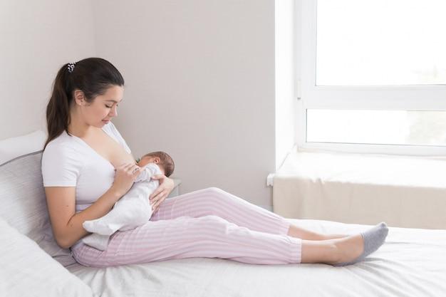 Jonge moeder borstvoeding, borstvoeding en knuffelen baby Premium Foto