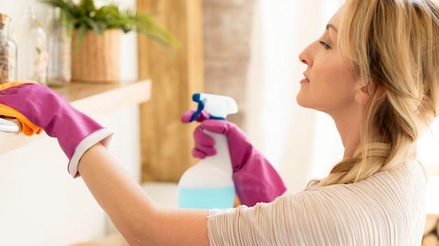Jonge moeder die het huis schoonmaakt Premium Foto