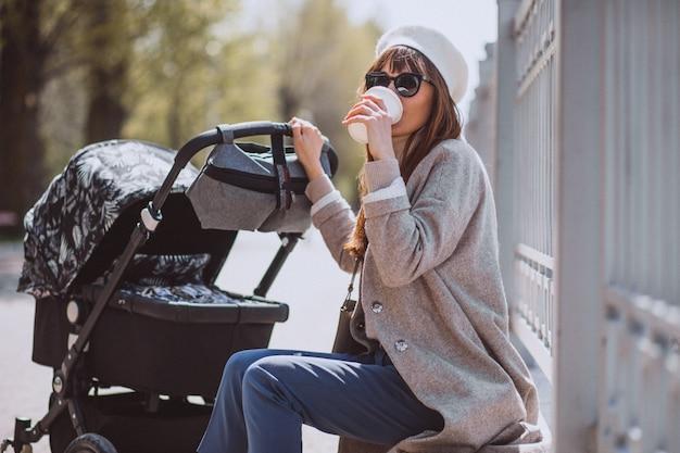 Jonge moeder die met kinderwagen in park loopt Gratis Foto