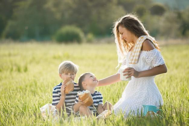 Jonge moeder die organische verse melk met haar kinderen in openlucht drinkt Premium Foto