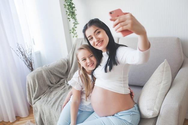 Jonge moeder die selfie met haar kleine dochter maakt. vrouw die baby verwacht. binnen en gelukkige familie. Premium Foto