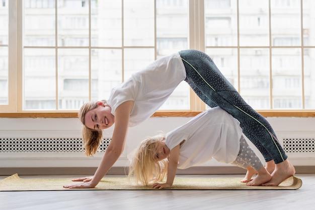 Jonge moeder die yoga met 3 jaar dochter voor venster doet. gelukkige moeder lacht tijdens het beoefenen van yoga samen met haar schattige meisje. naar beneden kijkende hondenasana Premium Foto