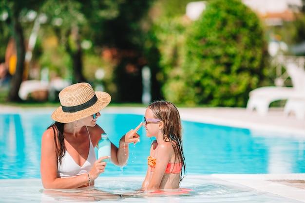 Jonge moeder die zonroom toepast op dochterneus Premium Foto
