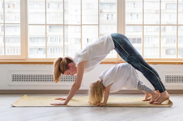 Jonge moeder doet yoga met 3-jarig meisje voor raam. neerwaartse hond asana pose Premium Foto