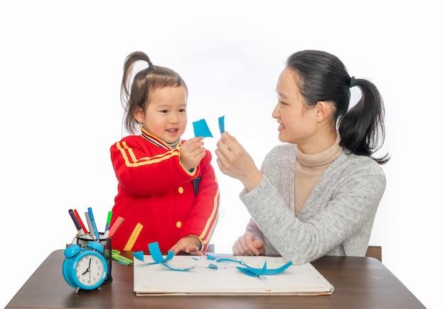Jonge moeder en dochter spelen papier gesneden Premium Foto