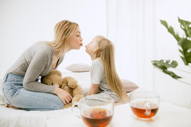 Jonge moeder en haar dochtertje thuis op zonnige ochtend. zachte pastelkleuren. gelukkige familietijd in het weekend. Gratis Foto