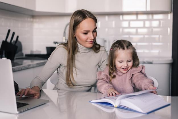 Jonge moeder en kinddochter die thuiswerk doen en thuis schrijven die lezen Gratis Foto