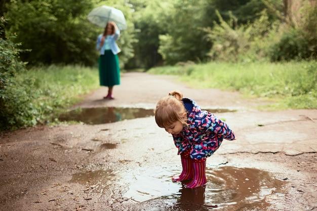 Jonge moeder en kleine dochter hebben plezier wandelen in rubberlaarzen op de zwembaden in het park Gratis Foto
