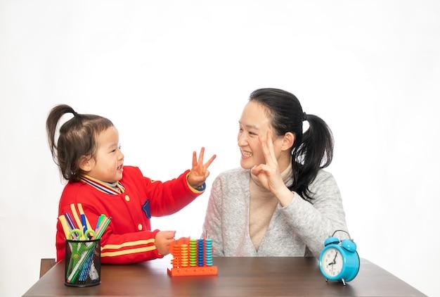 Jonge moeder leert haar dochter rekenen Premium Foto