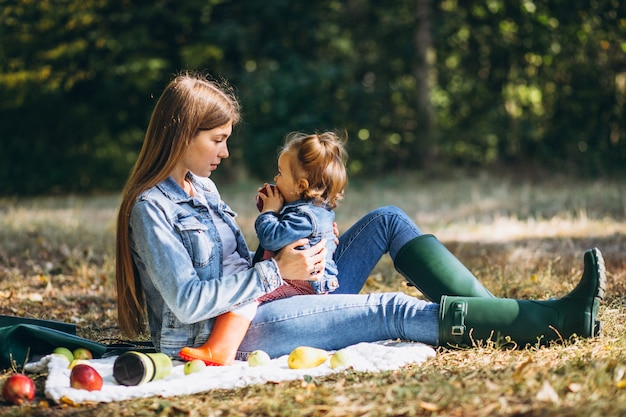 Jonge moeder met haar dochtertje in een herfst park met picknick Gratis Foto