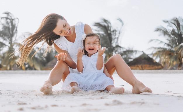 Jonge moeder met haar dochtertje op het strand aan de oceaan Gratis Foto