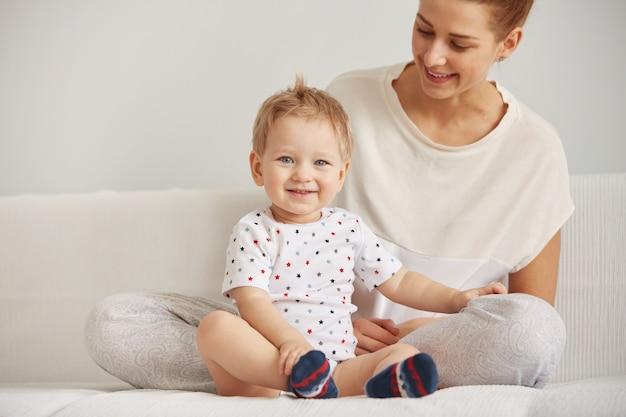 Jonge moeder met haar één jaar oude zoontje gekleed in pyjama's zijn ontspannend Gratis Foto