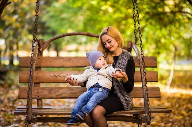 Jonge moeder met haar zoontje rust op een houten bankje in het herfst gouden park Gratis Foto