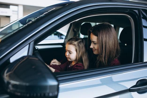 Jonge moeder met kleine dochter zit in een auto Gratis Foto