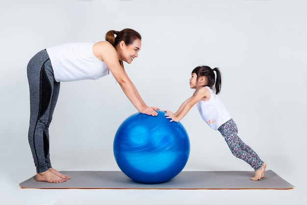 Jonge moeder met kleine dochteroefening op geschiktheidsbal Gratis Foto