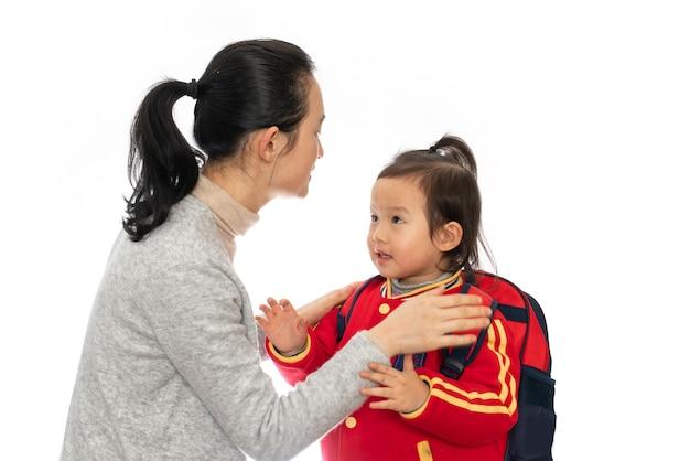 Jonge moeder stuurt haar dochter naar de kleuterschool Premium Foto