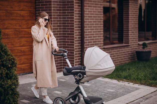Jonge moeder wandelen met kinderwagen Gratis Foto
