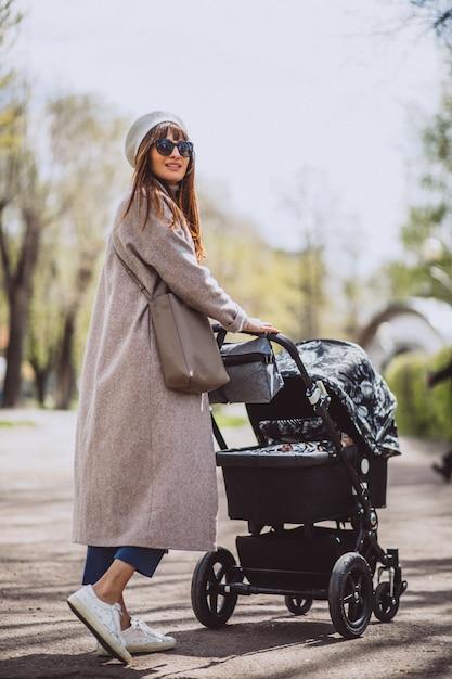 Jonge moeder zit met kinderwagen in park Gratis Foto