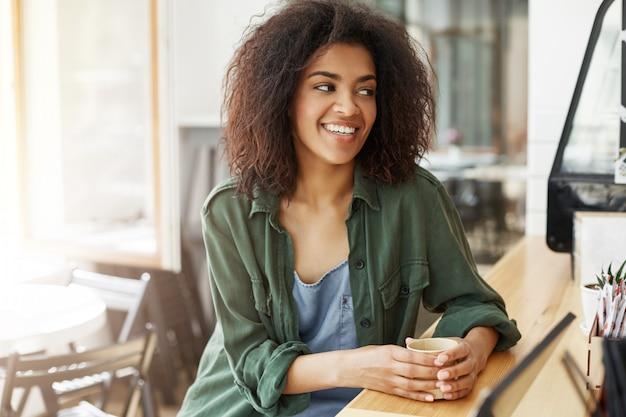 Jonge mooie afrikaanse studente die ontspannende zitting in koffie glimlachen die het drinken koffie glimlachen. Gratis Foto