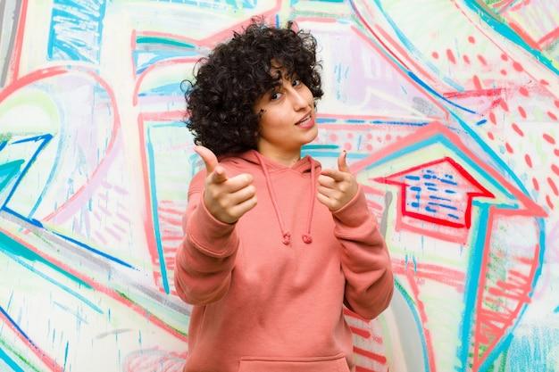Jonge mooie afrovrouw die met het positieve, succesvolle, gelukkige houding glimlachen glimlachen, die kanon maken ondertekenen met handen tegen graffitimuur Premium Foto