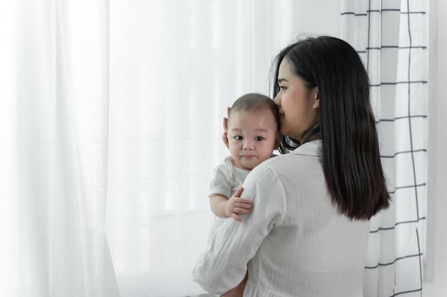Jonge mooie aisan-moeder met haar kleine schattige pasgeboren baby Premium Foto