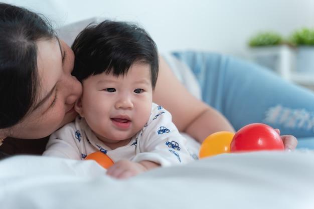 Jonge mooie aziatische moeder met aziatische baby op bed Premium Foto