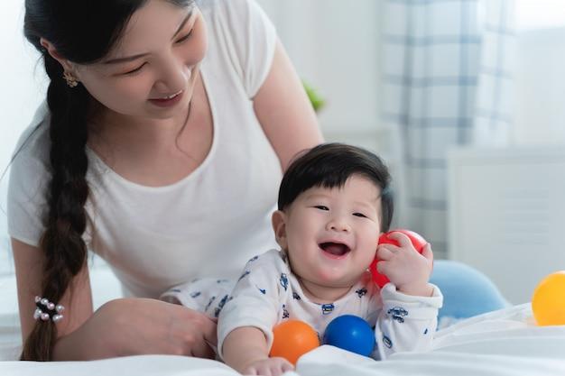Jonge mooie aziatische moeder met haar kleine schattige baby op bed. Premium Foto