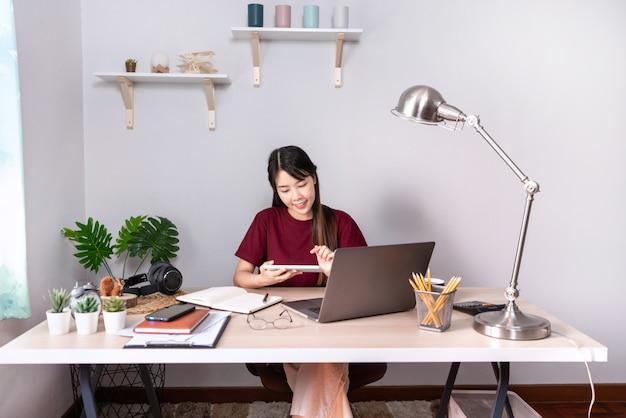 Jonge mooie aziatische vrouw die thuis werkt Premium Foto