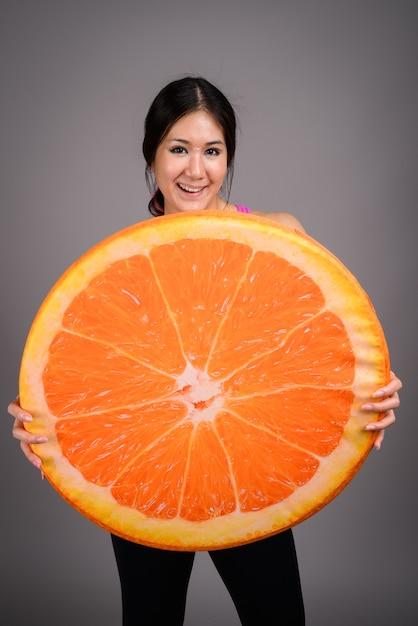 Jonge mooie aziatische vrouw klaar voor sportschool tegen grijze muur Premium Foto