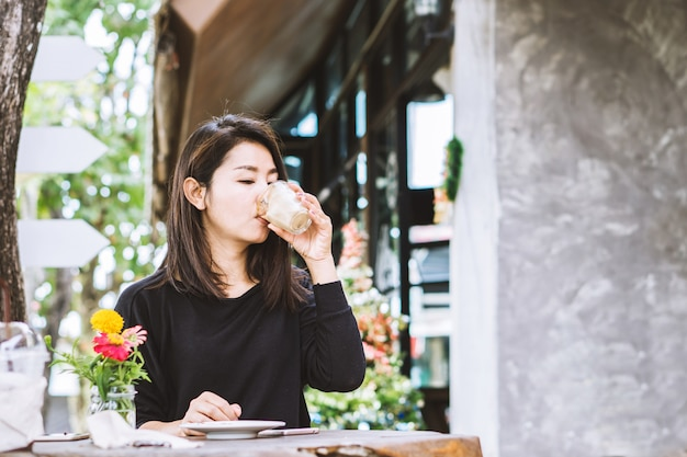 Jonge mooie aziatische vrouw koffie drinken buitenshuis Premium Foto